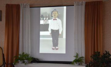 Film z uczestnikiem konkursu wyświetlony na ekranie przedstawiającym okno w pokoju