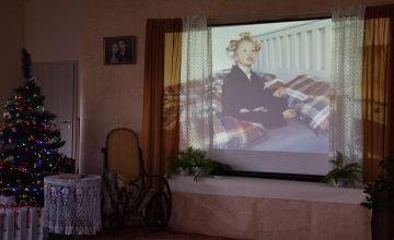 Film z uczestnikiem konkursu wyświetlony na ekranie przedstawiającym okno w pokoju, którym znajduje się świateczna choinka, stoliczek kawowy oraz bujak